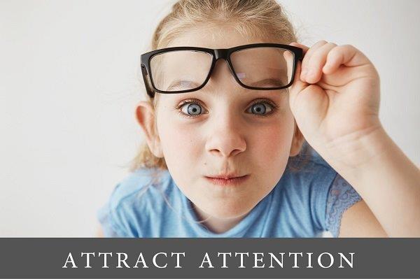 devojčica znatiželjno gleda sa naočarima koje je rukom podigla sa očiju