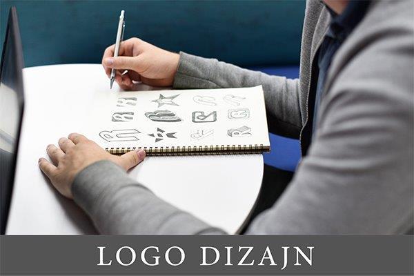 dizajner koji u svesci skicira različite logoe